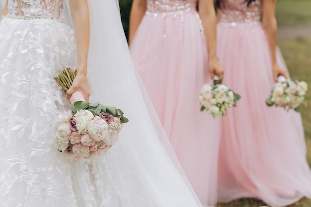 Fila di damigelle con mazzi di fiori alla cerimonia di nozze
