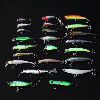 Fila di diversi esche da pesca su sfondo nero