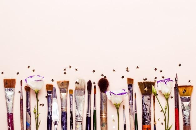 Fila di diversi pennelli e fiori. dispersione di stelle d'oro concetto di arte