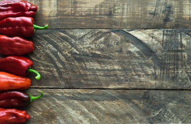 Fila di peperoni su fondo in legno. copia spazio
