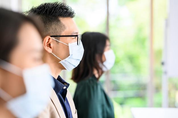 Fila di persone asiatiche indossare maschere protettive per la sicurezza