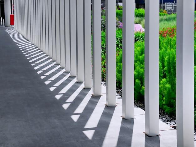 Fila di pilastri quadrati bianchi con luci e ombre sulla passerella