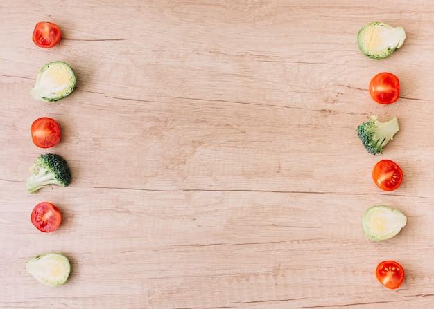 Fila di pomodorini tagliati a metà; cavoletti di bruxelles; broccoli sullo scrittorio di legno con lo spazio della copia per la scrittura del testo
