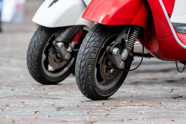 Fila di scooter classico parcheggio per strada. primo piano di una ruota anteriore.