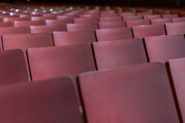 Fila di sedili di un vecchio cinema abbandonato