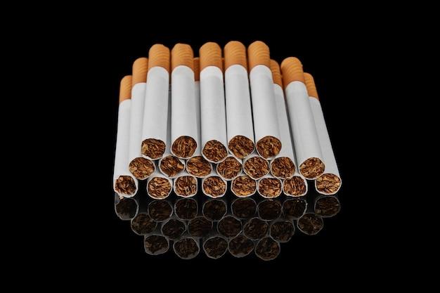 Fila di sigarette con filtro su una superficie nera lucida