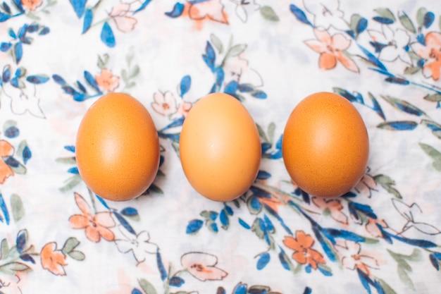 Fila di uova di gallina su materiale fiorito