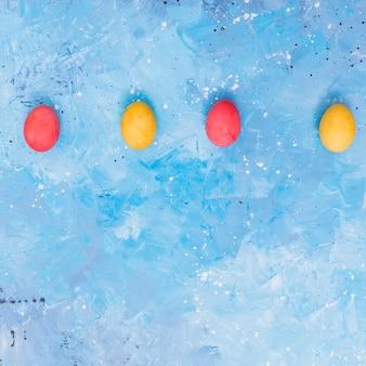 Fila di uova di pasqua colorate sul tavolo