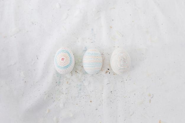 Fila di uova di pasqua con motivi e piume sul tessile
