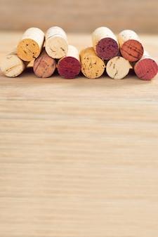 Fila di vecchi tappi per vino su fondo vago in legno con lo spazio della copia.