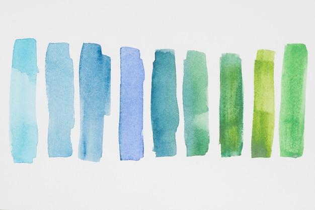 Fila di vernici verdi e blu su carta bianca