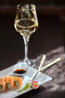 Filadelfia maki sushi rotoli con salmone, crema di formaggio, cetriolo su piatto bianco e bicchiere di vino