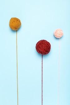 Filati colorati per maglieria, ferri da maglia e uncinetti, sfondo blu. vista dall'alto