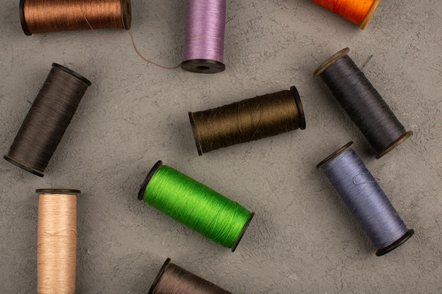 Filati cucirini colorati su una scrivania grigia