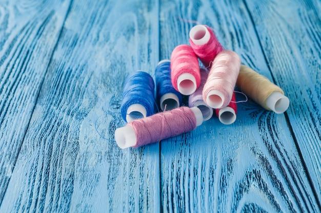 Filati cucirini colorati su una vecchia tavola di lavoro