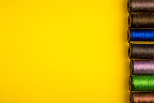 Filati cucirini multicolori allineati in uno sfondo giallo