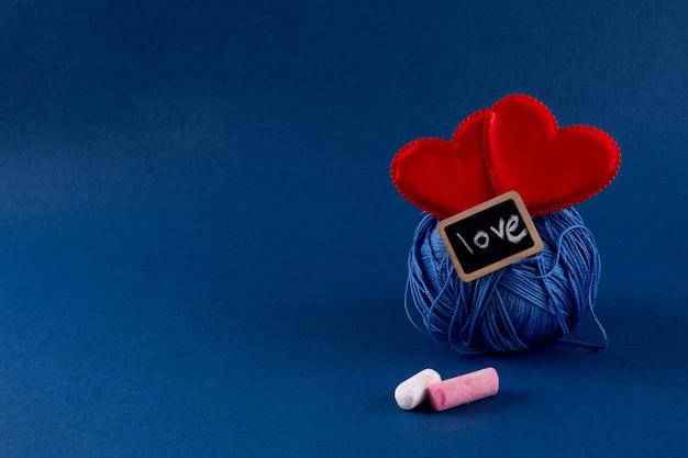 Filati per maglieria blu con i cuori rossi sul fondo blu classico di colore 2020. san valentino 14 febbraio concetto fai da te. copia spazio, vista dall'alto, banner.