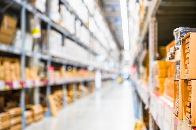 File degli scaffali con le scatole delle merci nel deposito moderno del magazzino di industria