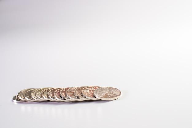 File delle monete argentate della peseta spagnola isolate su fondo bianco.
