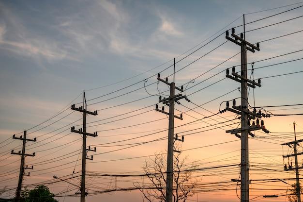 File rurali del palo di elettricità con la rete dei cavi sul tramonto