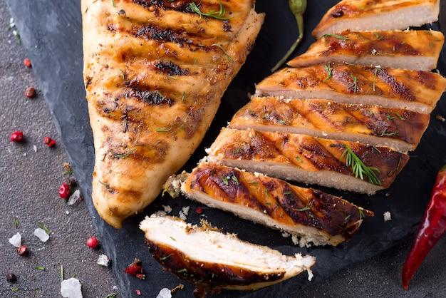 Filetti di pollo alla griglia sul piatto di ardesia su sfondo grigio cemento