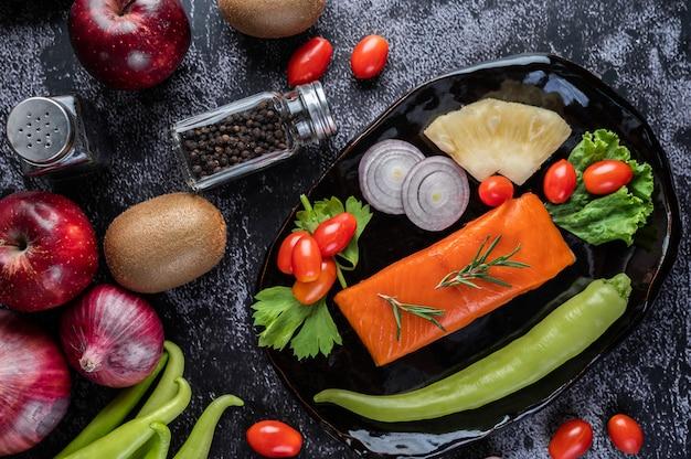 Filetti di salmone crudo, pepe, kiwi, ananas e rosmarino su un piatto e pavimento in cemento nero.