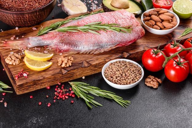 Filetto crudo di pesce persico del mar rosso preparato per la cottura con spezie ed erbe aromatiche