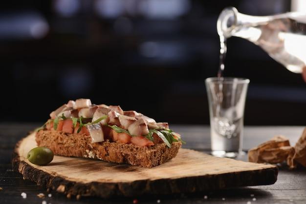 Filetto di aringhe con pomodoro su un pezzo di pane fritto. su un piatto blu
