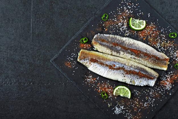Filetto di aringhe con sale marino e spezie su una tavola di pietra nera. filetti di aringhe norvegesi