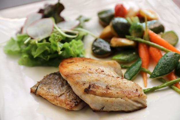 Filetto di branzino con verdure grigliate e insalata sul tavolo di legno