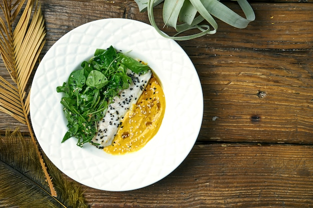 Filetto di branzino fritto appetitoso con salsa e rucola gialle in un piatto su un di legno