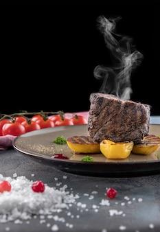 Filetto di bue mignon con fumo. patate al forno, salsa di mirtilli rossi, pomodorini su uno sfondo grigio cemento