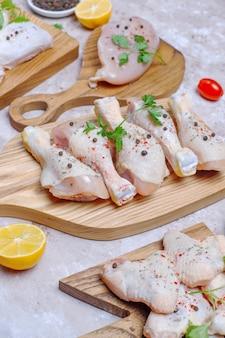 Filetto di carne di pollo crudo, coscia, ali e zampe con erbe, spezie, limone e aglio. vista dall'alto