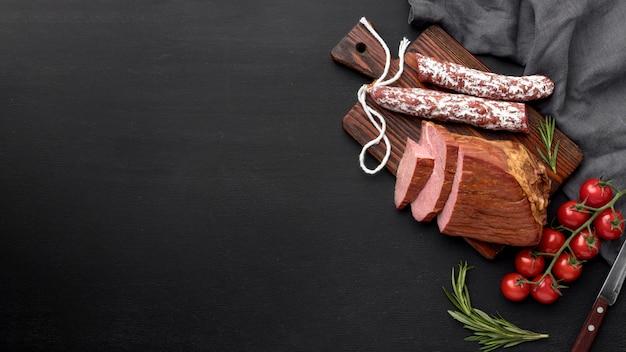 Filetto di carne e salame su tavola di legno con copia-spazio