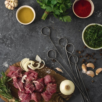 Filetto di manzo affettato con verdure. tavolo da cucina con ñ uts carne e verdure sulla vista del piano del tavolo scuro. ingredienti per cucinare la carne