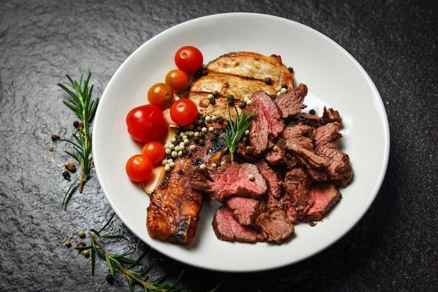 Filetto di manzo arrosto e braciole di maiale con erbe e spezie servire con verdure sul piatto bianco - fetta di carne di manzo alla griglia sulla superficie nera