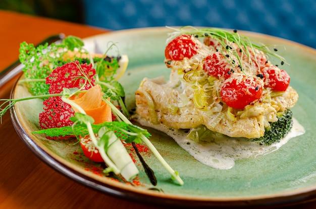 Filetto di merluzzo con pomodorini ciliegia e formaggio, servito con verdure e micro verdure. avvicinamento