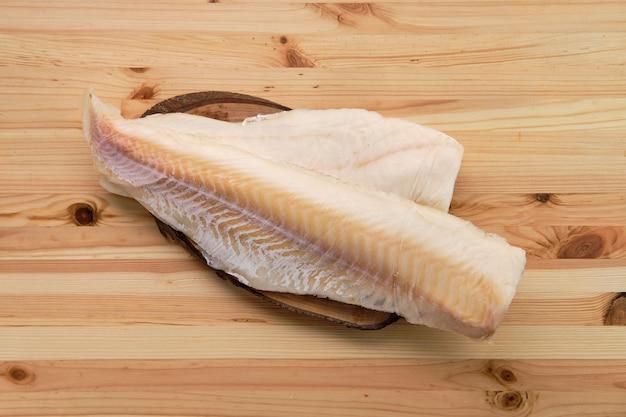 Filetto di merluzzo congelato sulla tavola di legno
