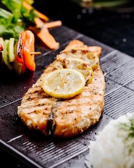 Filetto di pesce alla griglia con bastoncini di limone e verdure su una tavola di bistecca nera.