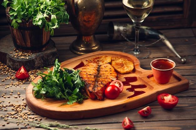 Filetto di pesce alla griglia con pomodoro, salsa rossa, erbe aromatiche e un bicchiere di vino bianco.