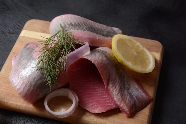 Filetto di pesce aringa su tavola di legno con pepe, erbe aromatiche, cipolla rossa e limone