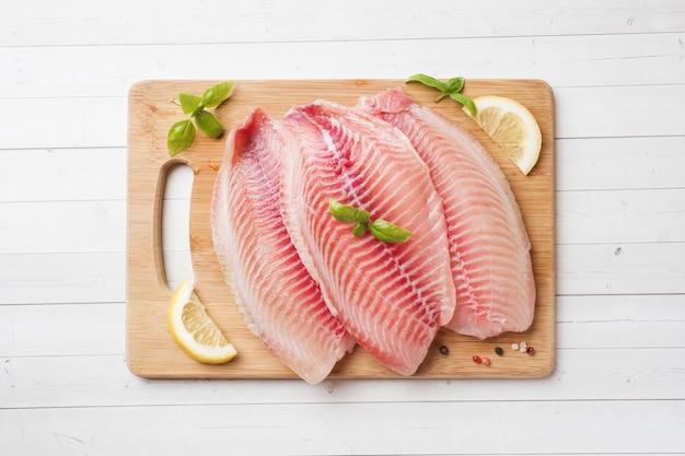 Filetto di pesce crudo di tilapia su un tagliere con limone e spezie