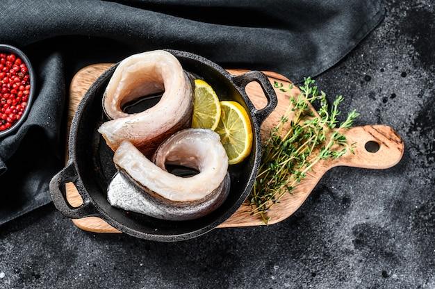 Filetto di pesce crudo fresco del nasello in una padella con pepe e limone.