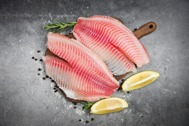 Filetto di pesce fresco affettato per bistecca o insalata con erbe spezie rosmarino e limone - filetto di tilapia crudo pesce e sale su fondo di pietra scura e ingredienti per cucinare cibo