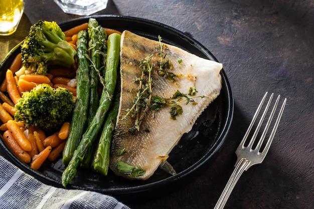 Filetto di pesce persico con asparagi, broccoli e carote.