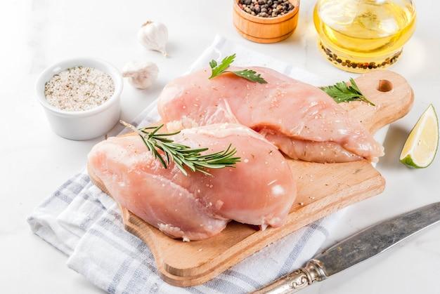Filetto di petto di pollo di carne cruda con erbe e spezie di olio d'oliva su fondo di marmo bianco
