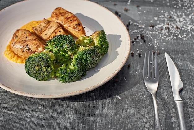 Filetto di petto di pollo fritto con salsa fruttata, broccoli sullo sfondo di legno, generoso spazio di copia