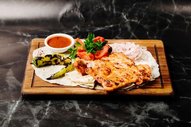 Filetto di pollo alla griglia in lavash con peperone verde grigliato, pomodori e salsa rossa.