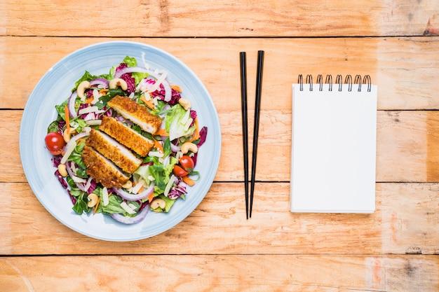 Filetto di pollo con insalata su piatto di ceramica; bacchette e blocco note a spirale in bianco sulla tavola di legno