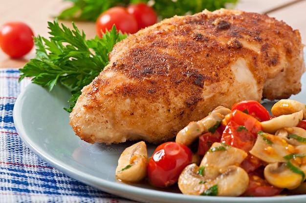 Filetto di pollo con pangrattato croccante guarnito con funghi e pomodori